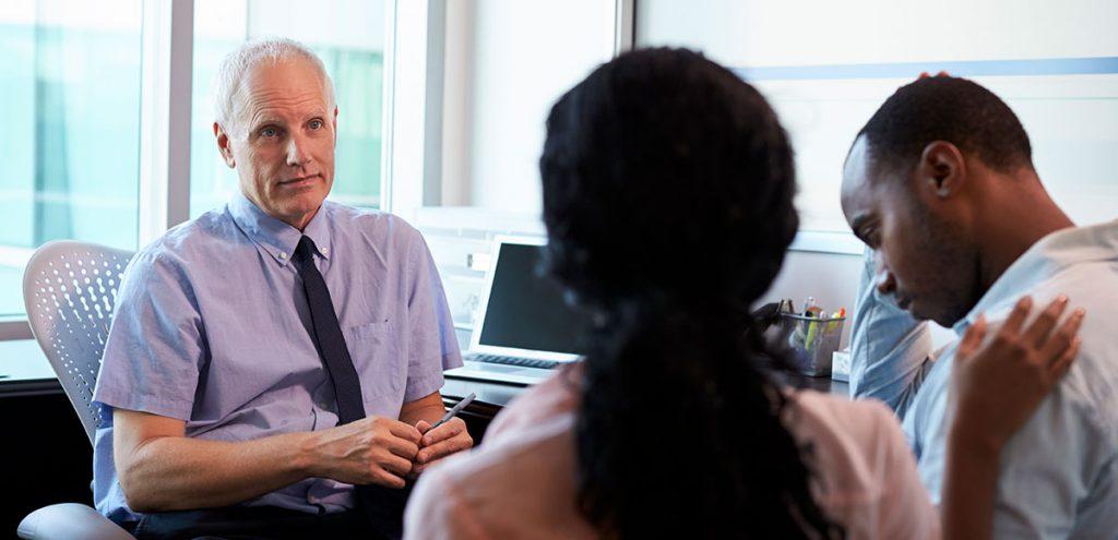 Médico conversando com um casal preocupado sobre sintomas de infertilidade