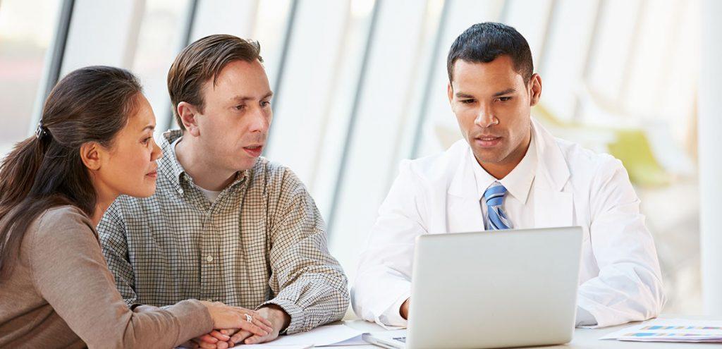 Casal conversando sobre infertilidade com um médico olhando um laptop