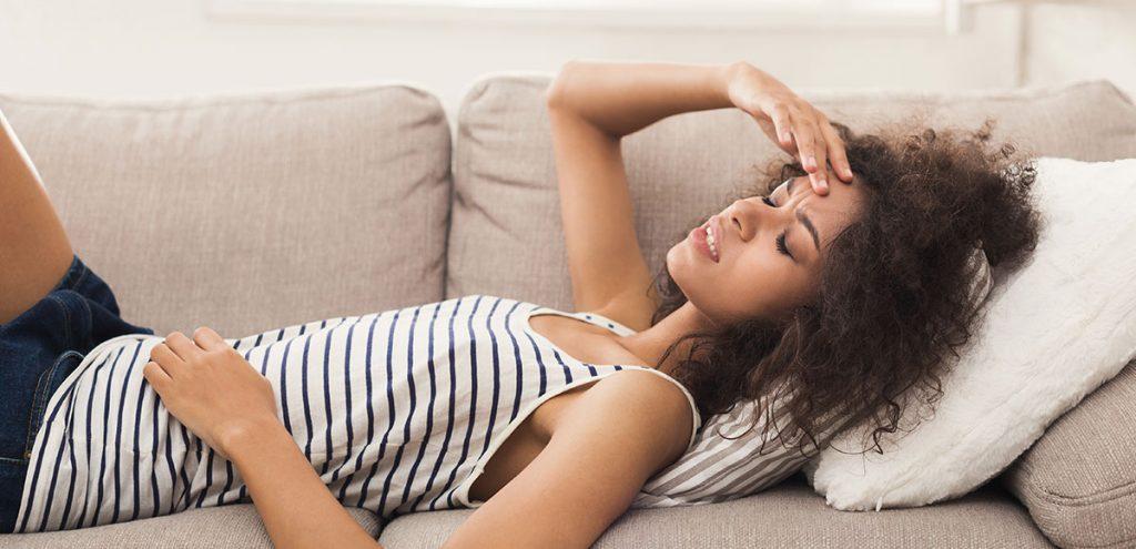 Mulher deitada no sofá com endometriose causa infertilidade